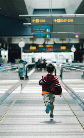 A small boy running in an airport