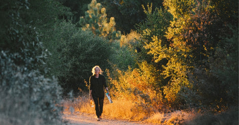 A woman walking in the fall to absorb the sun and feel better during the shorter fall days.