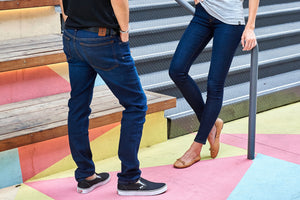 Image includes a man and women facing each other and wearing the Best Travel Jeans in the World in blue indigo jeans. The image is cropped from their waist down to their shoes. She is wearing skinny fit jeans while he is wearing tailor fitted jeans.