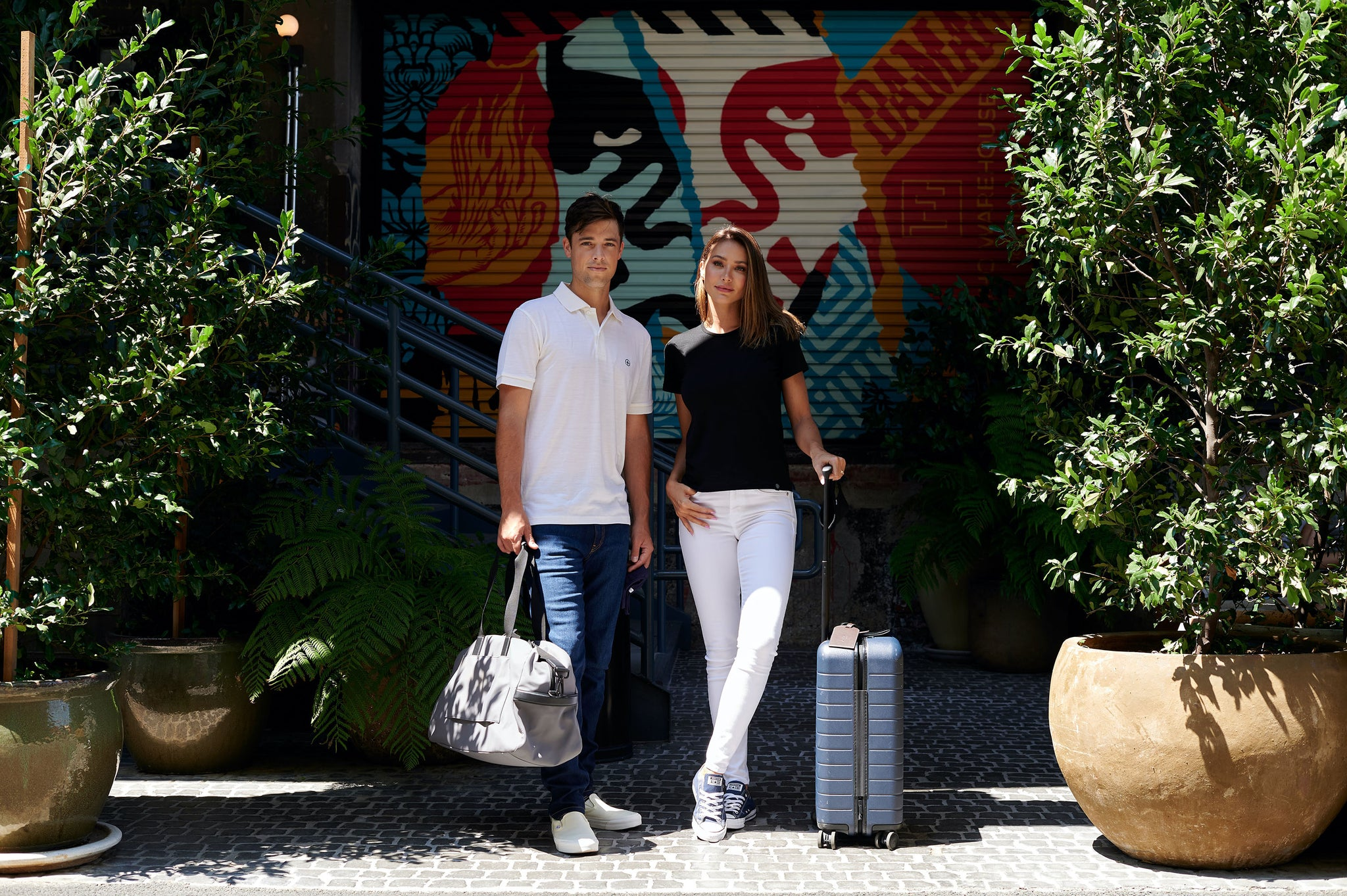 Lifestyle image of a man and women wearing Aviator outside of a trendy hotel. He is wearing a white polo shirt and indigo jeans. She is wearing a black crew neck t-shirt and white skinny jeans.