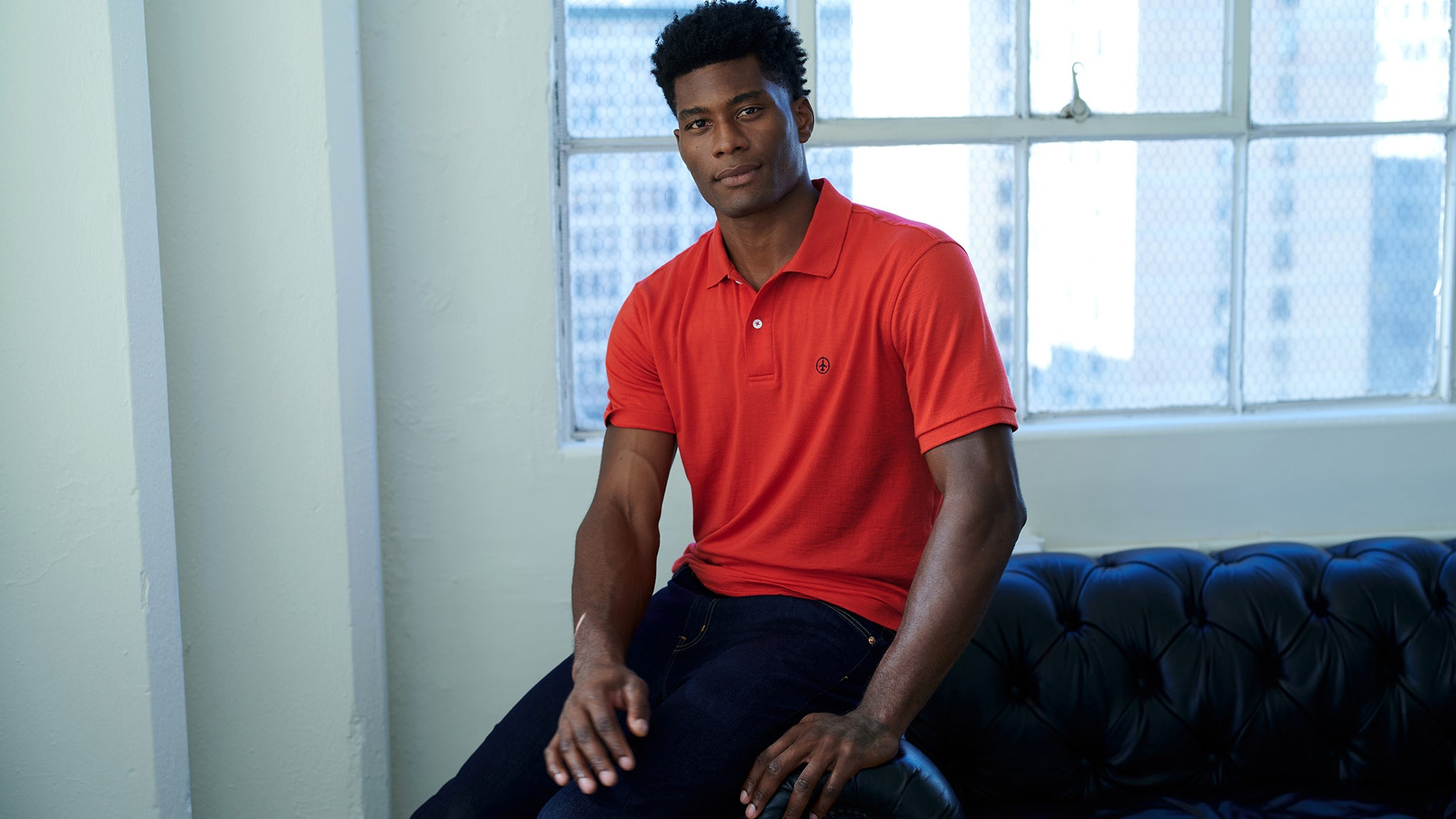 African American man wearing an Air Dry Merino Wool Polo in red with a navy blue chest logo embroidery. He is sitting on the arm of a black leather sofa next to the window.