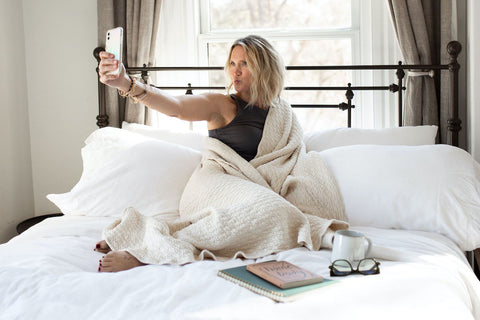 Woman on bed with cell phone. Is your bedroom making you sick?