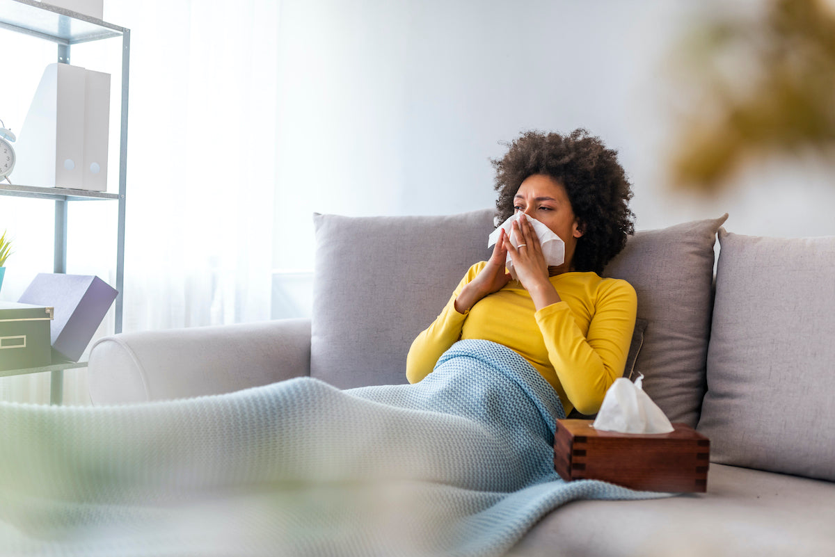woman with cold blowing nose sitting on couch