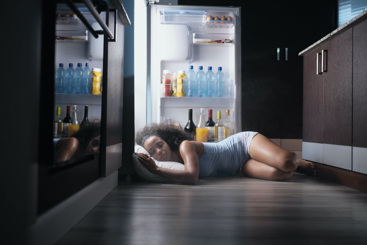 woman with night sweats hot flash sleeping in front of fridge