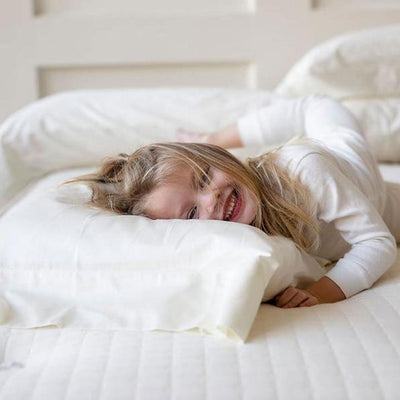 Little girl on bed smiling as she enjoys the comfort of the Devotion Mattress