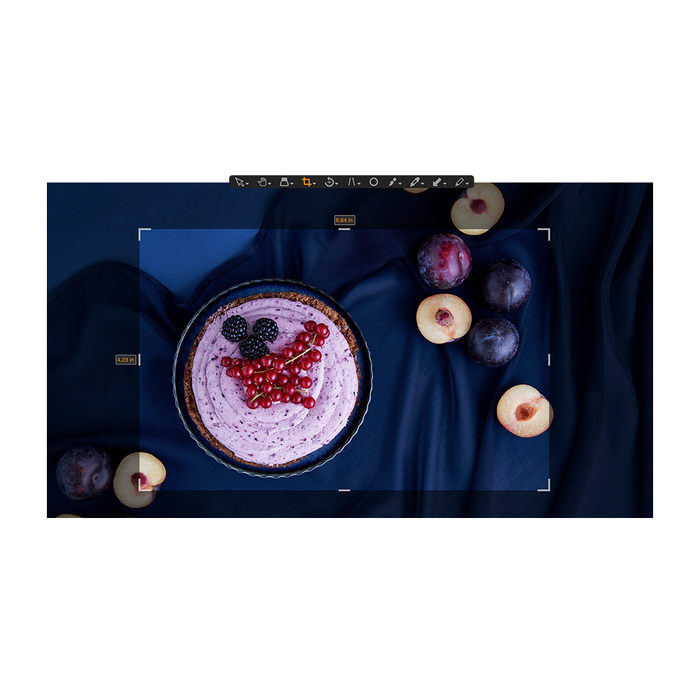 The Capture One Pro 20 cropping tool, cropping an image of a mixed berry pie and plums against a silky navy backdrop.