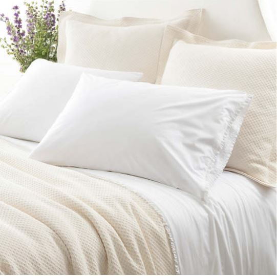 luna ruffle sheet set is shown on bed showing tiny ruffle on top of top sheet as well as edges on pillow cases mixed with ivory bedding