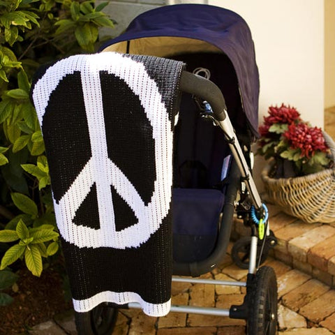 remy cashmere blanket with white peace sign on black background shown on stroller
