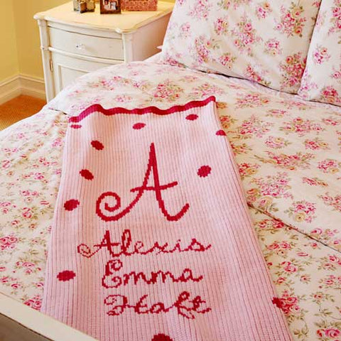alexis emma cashmere blanket shown with A for intial with Alexis Emma Haft below on light pink with red writing, polka dots and border