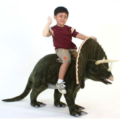 boy sitting on tristan the triceratops who is shown in green olive plush trimmed with cream with cream horns