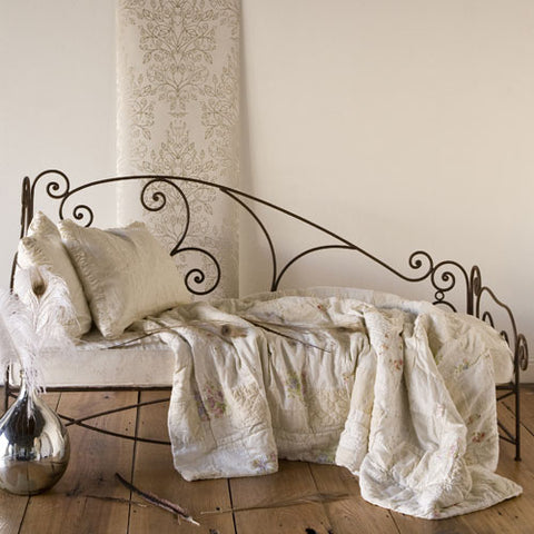 valerie daybed shown in black iron with curly cue detailing show with neutral pillows and blanket
