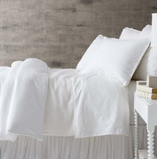 another image showing side profile of luna ruffle sheet set on bed in white with ruffle edge on top of top sheet with pillow case with same ruffle edging in white