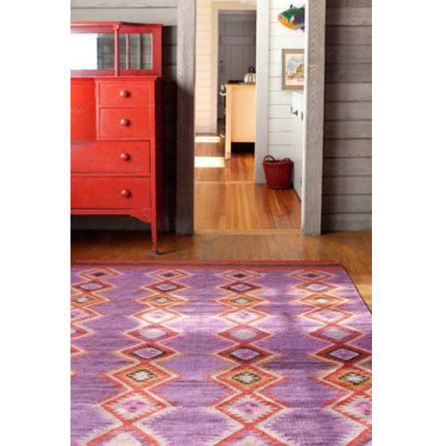frida rug shown in room showing azteca pattern in reds on a lavender and pink background