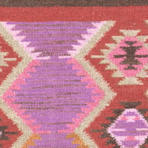 close up of azteca pattern on frida rug with reds, purples and pinks