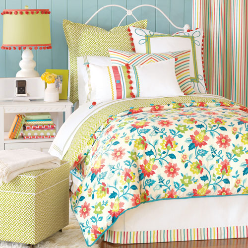 ashlynn bedding shown on bed with floral duvet with pom pom and stripe accent pillows