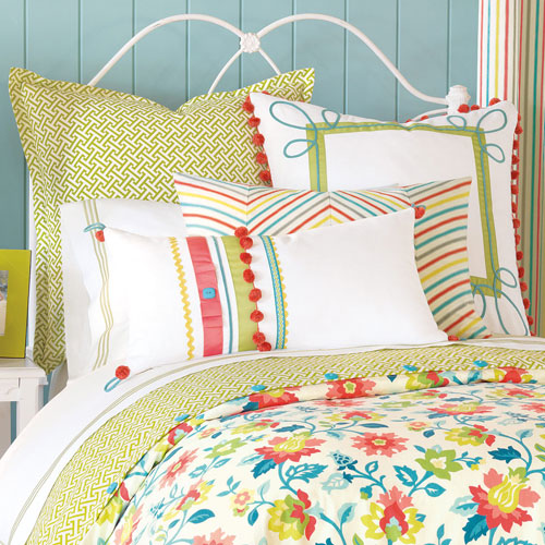 close up of ashlynn floral bedding with accent pom pom and stripe pillows