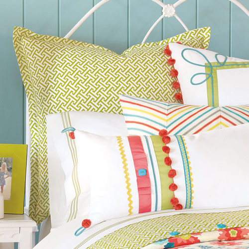 ashlynn sham shown as back pillow on white iron bed with other colorful accent pillows