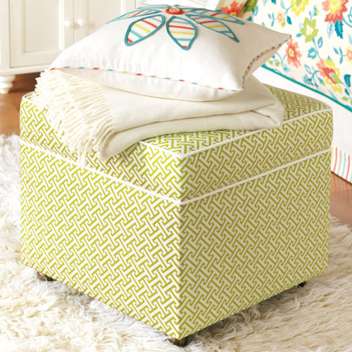 ashlynn storage ottoman is a cube in a green and white lattice pattern and welted with white shown in bedroom with throw blanket and accent pillow on top