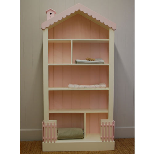 olivia dollhouse bookcase is shown in a taller version with pink beadboard, scalloped roof trim with pink birdhouse and pink fencing at the bottom, base color is white