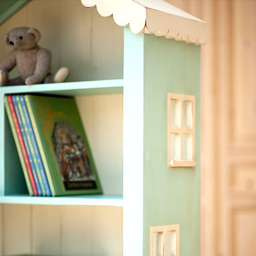 close up of olivia bookcase in blue with cream scalloped roof and windows