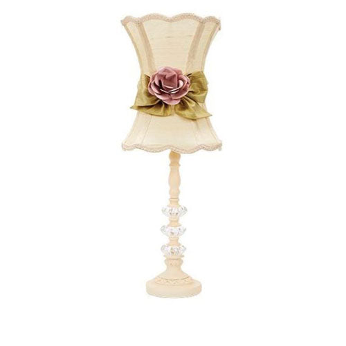 hazel table lamp has a three glass balls with ivory finish with a scalloped ivory lamp shade with green ribbon with rose in center