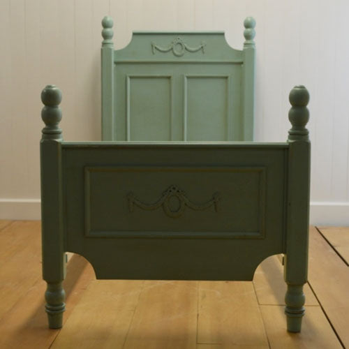 elsie bed shown in a seafoam finish straight on photo showing good view of headboard and footboard with wreath appliques