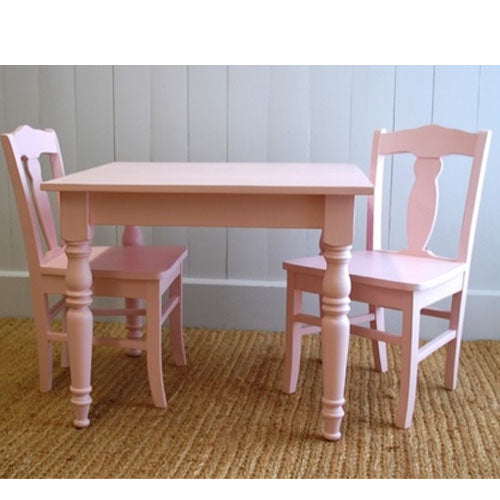 mabel light pink table and two chairs shown with traditional poster legs shown on sisal rug with white beadboard in the back