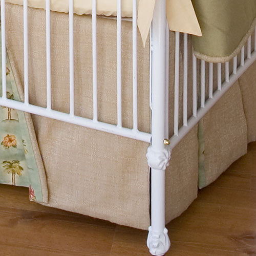 close up of kennedy iron crib feet shown in white with linen bedskirt