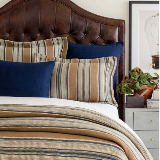 phoenix bedding showing on a brown leather headboard blue and taupe stripes with navy accent shams