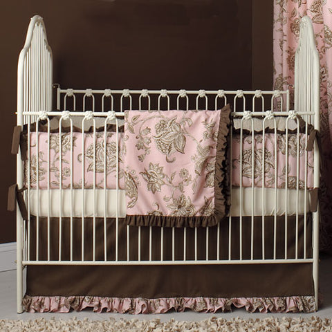 penny iron crib shown in antique white with pink and brown linens in nursery