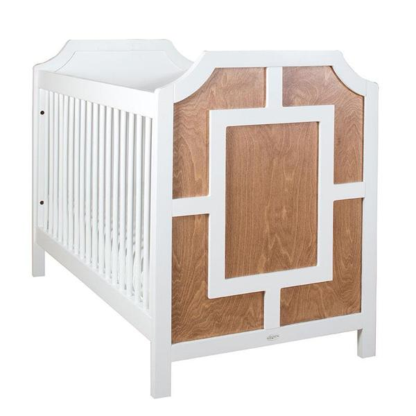 carter crib shown in white with caramel on exterior of headboard ends shown with white decorative molding on headboard exterior forming a vertical rectangle