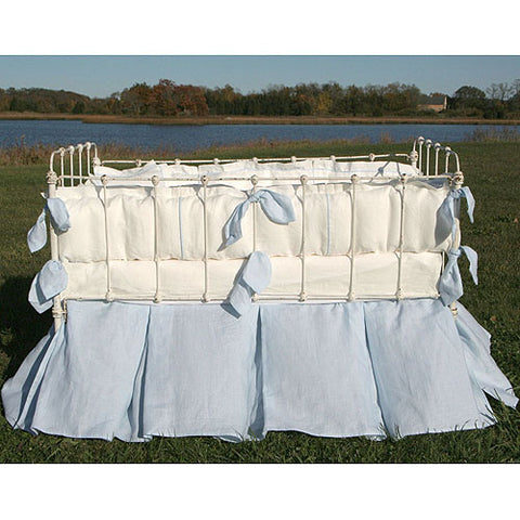 summer baby bedding shown outside on white iron crib with baby blue skirt, white sheet and bumper with accented blue ties