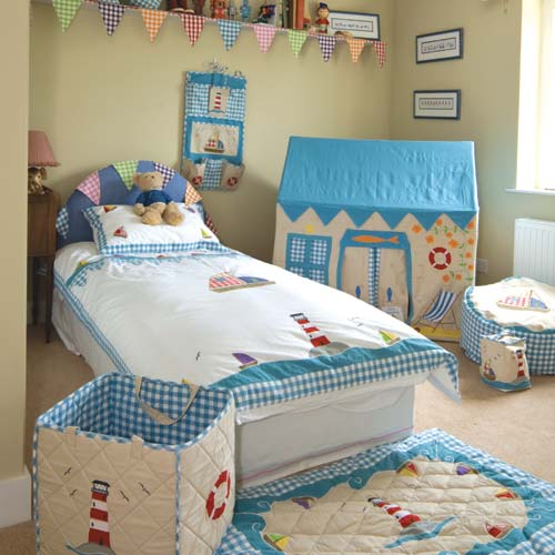 lighthouse beach playhouse shown accented with blue and white gingham showing matching quilt, toy bag, bean bag and bedding all shown in child's bedroom