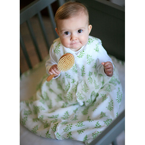 baby wearing sleep sack in green vine version over white