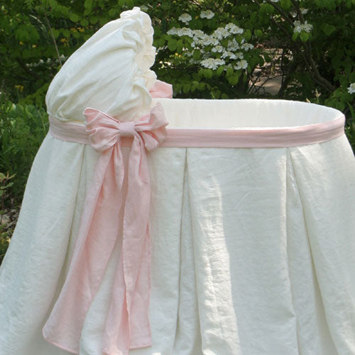 close up of emery bassinet shown in irish linen in ivory with baby pink sash and bow
