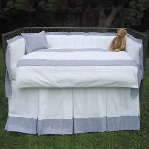 adelaide bedding shown on iron crib outdoors in white with accents of blue and navy gingham with teddy bear in right corner and accent pillow in left corner