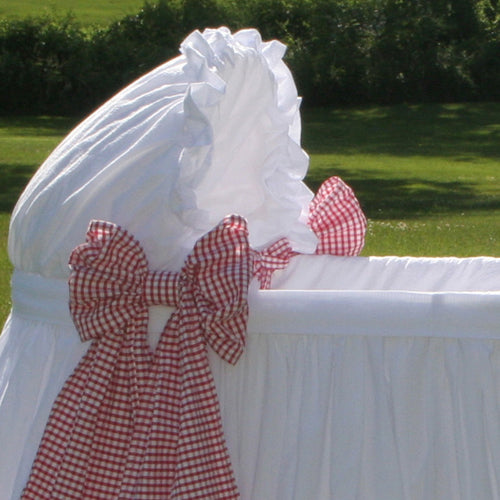 close up of ida bassinet showing close up of white cotton bassinet hood and red and white gingham side bows