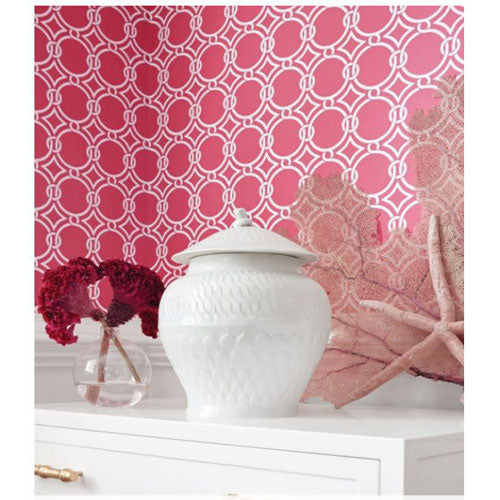 lula wallpaper in raspberry with a circle pattern linked together in white on top of raspberry shown in bedroom