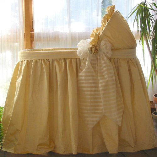 remi bassinet shown in cream dupioni silk with white sheer silk organza bow with vertical stripes on bow tails