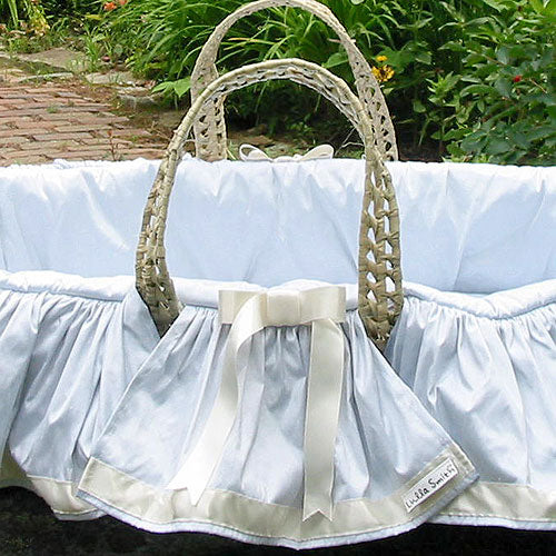 close up of colson moses basket in soft blue and ivory dupioni silk showing close up of hand tied silk ribbons