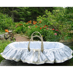 colson moses basket seamed in soft blue dupioni silk with ivory trim with silk ribbon shown outdoors