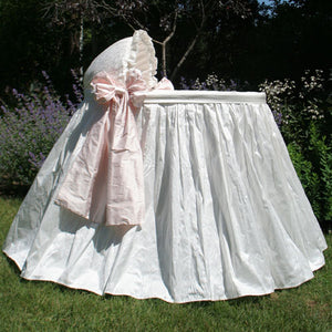jada bassinet shown outdoors in white silk with pink blush side bows with ruffled bassinet