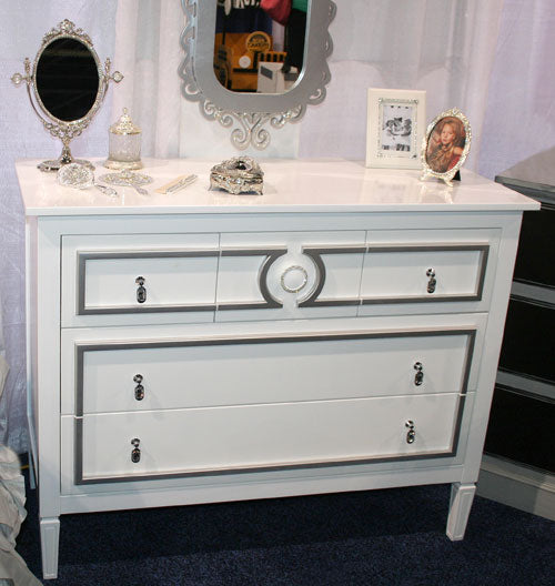 diaz dresser showing a total of five drawers shown in white with silver accented lines around drawer fronts with crystal tear drop hardware