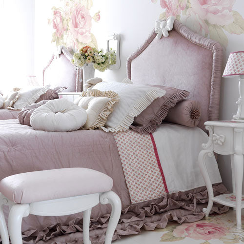 makenna upholstered bed shown in rose silk in bedroom with bedding and throw pillows, night stand and vanity seat
