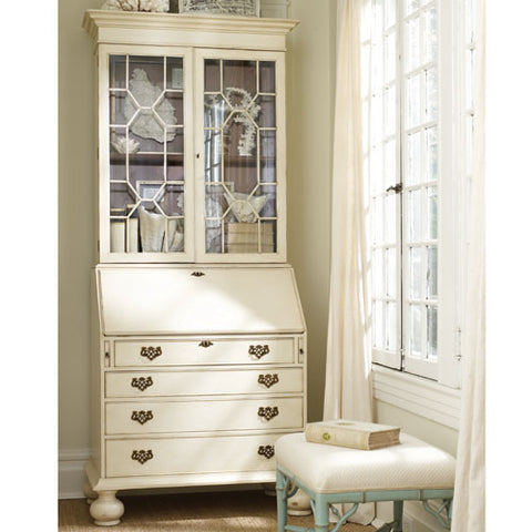 lois secretary shown in living room with four drawers with secretary desk and glass doors with intricate designed doors shown in vanilla bean finish with antique drawer pull hardware