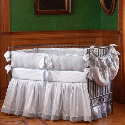 smith baby bedding shown in ice silk with blue velvet border on crib skirt with piped crib bumper and toy bag shown on iron crib