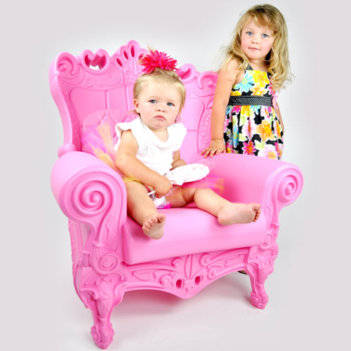 trudy youth chair shown in bright pink with baby sitting in chair with girl beside her