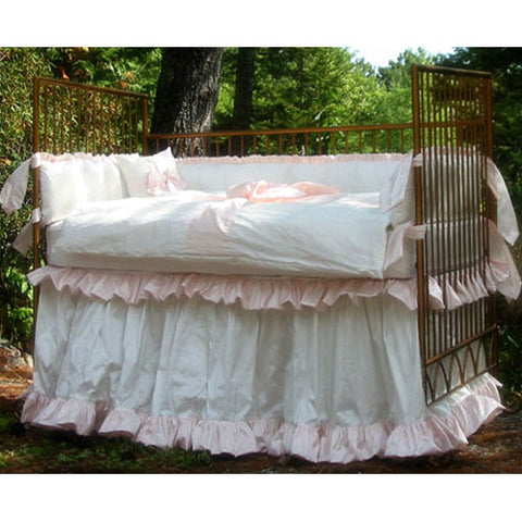 lexi baby bedding shown on antique iron crib in white and pink silk shown outdoors