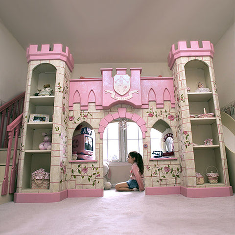 gia's castle loft bed shown with girl sitting in play area with castle painted in pink and cream with hand painted pink roses with stairs on the left and slide on the right with bed above