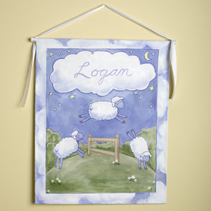 counting sheep personalized wall hanging is personalized with Logan in the white cloud and features three sheep including one jumping over the fence